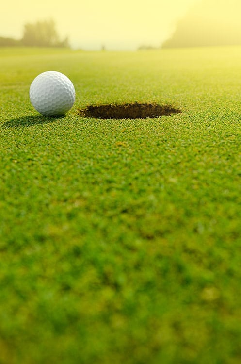 Golfball am Loch liegend auf Rasen